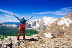 一名妇女在山天夏天 岩石路线 蓝天 雪和 图库摄影