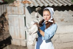 一名妇女在村庄拿着一只鹅 在减速火箭的样式的射击 免版税库存照片
