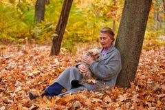 一名妇女坐在树下并且拿着在她的胳膊的一条狗 室外在秋天公园 免版税库存照片