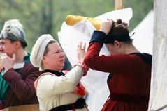 一名妇女帮助别的穿上帽子 免版税图库摄影