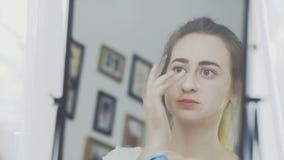 一名妇女或在她的面孔的化妆面具的画象有奶油的 影视素材