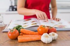 一名妇女的中间部分有食谱书和菜的在厨房里 库存图片