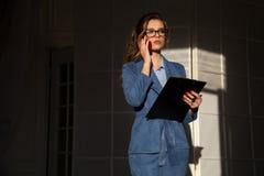 一名妇女的企业画象一套西装的有智能手机的和纸的一个文件夹 库存照片
