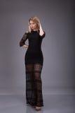 一名妇女的全长画象黑晚礼服的在灰色背景 库存图片