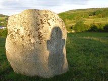 一名妇女的剪影一块古老石头的 库存图片
