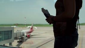 一名妇女的剪影在有护照和登机牌的机场终端 股票录像