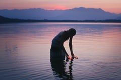 一名妇女的剪影在紫色湖浇灌 库存图片