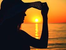 一名妇女的剪影太阳帽子的在海在黎明 库存图片
