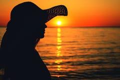 一名妇女的剪影太阳帽子的在海在黎明 图库摄影