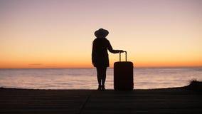 一名妇女的剪影带着一个手提箱的在日落的海滩 股票录像