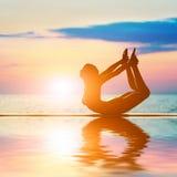 一名妇女的剪影弓瑜伽位置的 免版税图库摄影