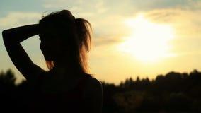 一名妇女的剪影接触她的日落的 股票视频