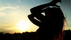 一名妇女的剪影接触她的日落的 股票录像
