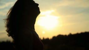 一名妇女的剪影接触她的日落的 影视素材