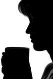 一名妇女的剪影有一个杯子的在手上 免版税图库摄影