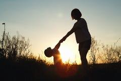 一名妇女的剪影有她的孩子的日落的 免版税库存照片