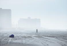 一名妇女的剪影有雾的城市海滩的 选择聚焦 免版税库存图片