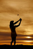 一名妇女的剪影有高尔夫俱乐部摇摆的 免版税图库摄影