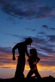 一名妇女的剪影比基尼泳装跪边亲吻的由牛仔决定 库存图片