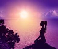 一名妇女的剪影海滩的 瑜伽和凝思 库存照片