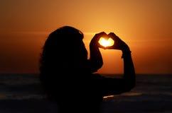 一名妇女的剪影用她的形成心脏的手,在海滩的日落 免版税库存照片
