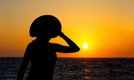 一名妇女的升剪影帽子的在五颜六色和生动的日落背景 免版税库存照片