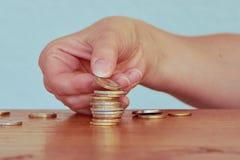 一名妇女的手有堆的一枚和两枚欧洲硬币 免版税库存照片