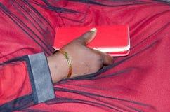 一名妇女的手有金镯子的和在猩红色的一个手机穿戴 免版税图库摄影