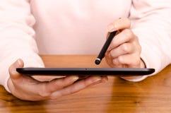 一名妇女的现有量有接触笔和片剂计算机的 库存图片