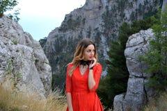 一名妇女的画象一件长的猩红色礼服的在山的一个森林里 免版税库存图片