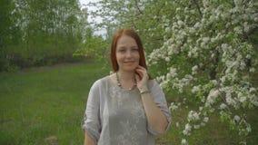 一名妇女的画象在一个美丽的开花的庭院里 股票录像