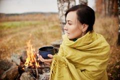 一名妇女的画象有一个杯子的热的茶在他的手秋天 免版税图库摄影