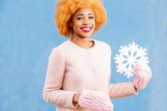 一名妇女的画象有人为雪花的在蓝色背景 免版税图库摄影