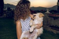 一名妇女的画象有她的小狗的在她的胳膊 免版税库存图片