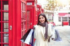 一名妇女的画象有购物带来的在她的在红色电话亭前面的手上在伦敦,英国 免版税库存图片
