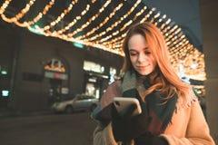 一名妇女的画象站立反对夜城市的背景和使用智能手机的衣服暖和的 免版税库存图片