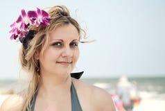 一名妇女的纵向有兰花的在她的在海滩的头发 免版税库存图片
