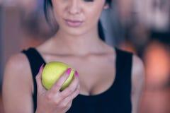 一名妇女的躯干用在黑暗的背景的一个绿色苹果 图库摄影