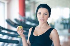 一名妇女的躯干用在黑暗的背景的一个绿色苹果 免版税库存照片