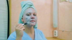 一名妇女的面孔有一块毛巾的在她的有一把刷子的头在皮肤面具 平均计划 股票录像