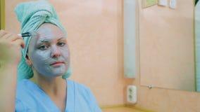 一名妇女的面孔有一块毛巾的在她的有蓝色黏土刷子的头在她的皮肤的 平均计划 调查 股票录像