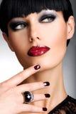 一名妇女的面孔有美丽的黑暗的钉子和性感的红色嘴唇的 免版税库存照片
