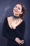 一名妇女的魅力项链画象黑色的 图库摄影