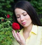 一名妇女的画象有一朵红色玫瑰的在庭院里 免版税库存图片