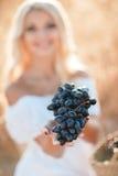 一名妇女的画象用葡萄在手上 免版税库存图片