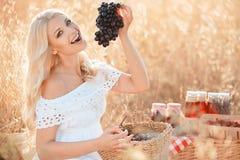 一名妇女的画象用葡萄在手上 库存图片