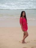 一名妇女的画象穿桃红色礼服的一个热带海滩的 库存照片