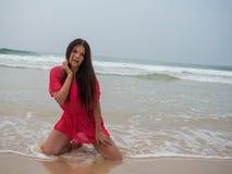 一名妇女的画象穿桃红色礼服的一个热带海滩的 免版税图库摄影