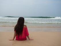 一名妇女的画象穿桃红色礼服的一个热带海滩的 免版税库存图片