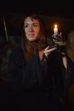 一名妇女的画象黑暗的与一个蜡烛 库存图片